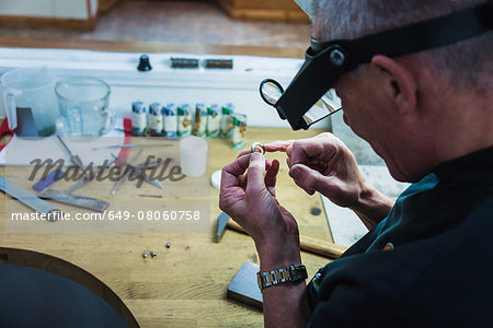 Jewellery craftsman touching platinum ring for smoothness Stock Photo - Premium Royalty-Free, Image code: 649-08060758