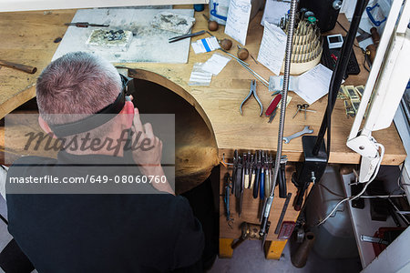 Overhead view of jewellery craftsman at workbench Stock Photo - Premium Royalty-Free, Image code: 649-08060760