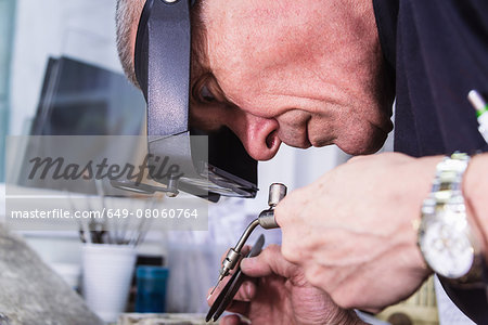 Close up of jewellery craftsman using miniature blowtorch Stock Photo - Premium Royalty-Free, Image code: 649-08060764