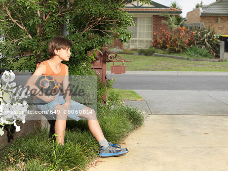 Sullen boy sitting on suburban wall holding soccer ball Stock Photo - Premium Royalty-Free, Image code: 649-08060814