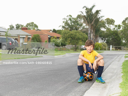 Portrait of boy sitting on soccer ball on suburban road Stock Photo - Premium Royalty-Free, Image code: 649-08060815