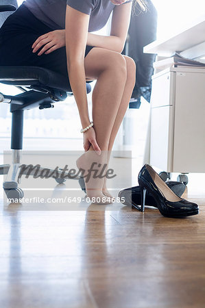 Neck down view of businesswoman massaging ankle at office desk Stock Photo - Premium Royalty-Free, Image code: 649-08084685