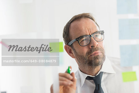 Businessman writing ideas on adhesive notes for glass wall Stock Photo - Premium Royalty-Free, Image code: 649-08084879