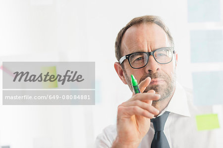 Businessman working on ideas at office glass wall Stock Photo - Premium Royalty-Free, Image code: 649-08084881