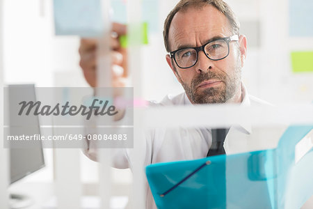 Businessman sticking adhesive notes to glass wall in office Stock Photo - Premium Royalty-Free, Image code: 649-08084883