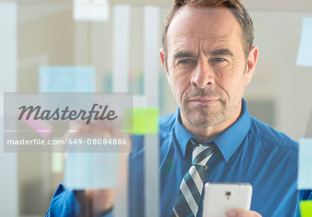 Businessman with smartphone sticking notes on office glass wall Stock Photo - Premium Royalty-Free, Image code: 649-08084886