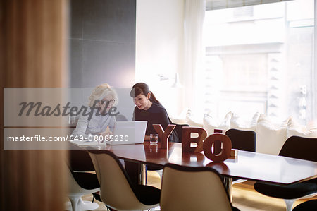 Two mature businesswomen using laptop at boardroom table Stock Photo - Premium Royalty-Free, Image code: 649-08085230