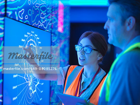 Female geologist with colleague studying graphical display of oil and gas bearing rock on screens Stock Photo - Premium Royalty-Free, Image code: 649-08085276