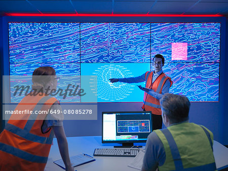 Geologists studying graphical display of oil and gas bearing rock on screens Stock Photo - Premium Royalty-Free, Image code: 649-08085278