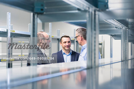 Businessmen and manager chatting in empty factory warehouse Stock Photo - Premium Royalty-Free, Image code: 649-08085784