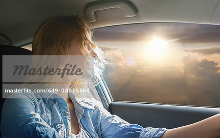 Woman driving car and watching sunset Stock Photo - Premium Royalty-Free, Image code: 649-08085864