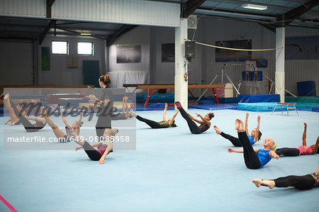 Gymnastics instructor overseeing class practising stretches Stock Photo - Premium Royalty-Free, Image code: 649-08085958