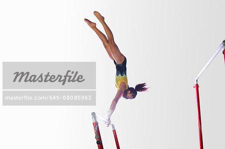 Young gymnast performing on uneven bars Stock Photo - Premium Royalty-Free, Image code: 649-08085963