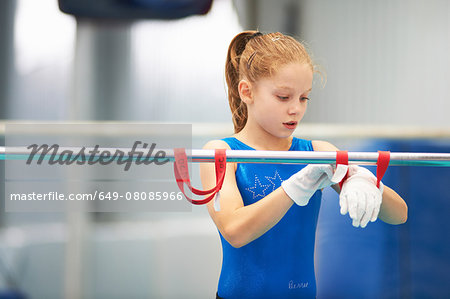 Young gymnast using training wrist straps to aid practise on bars Stock Photo - Premium Royalty-Free, Image code: 649-08085966