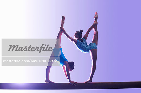 Two young gymnasts performing on balance beam Stock Photo - Premium Royalty-Free, Image code: 649-08085972