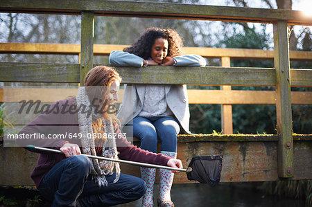 Couple fishing on bridge in countryside