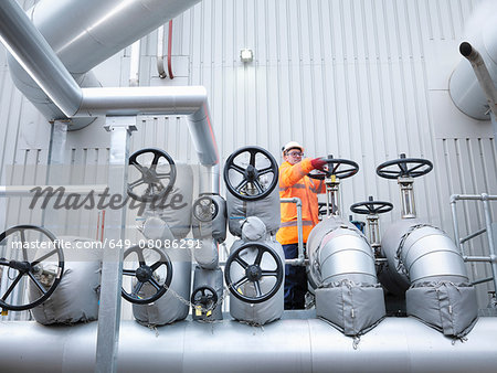 Worker turning valve of gas fired power station Stock Photo - Premium Royalty-Free, Image code: 649-08086291