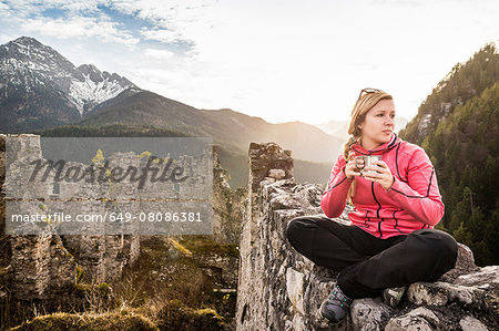 Young woman drinking coffee on top of Ehrenberg castle ruins, Reutte, Tyrol, Austria Stock Photo - Premium Royalty-Free, Image code: 649-08086381