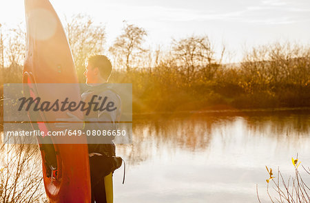 Young man holding kayak by lake Stock Photo - Premium Royalty-Free, Image code: 649-08086650