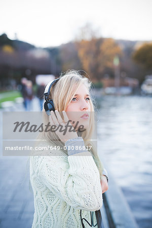 Young woman looking up whilst listening to headphones on lakeside, Como, Italy Stock Photo - Premium Royalty-Free, Image code: 649-08086817