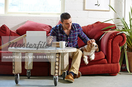 Mid adult man writing address on parcels whilst petting dog in picture framers Stock Photo - Premium Royalty-Free, Image code: 649-08086938