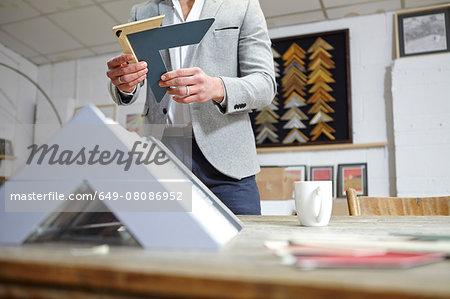 Surface level view of framer selecting frame in picture framers workshop Stock Photo - Premium Royalty-Free, Image code: 649-08086952