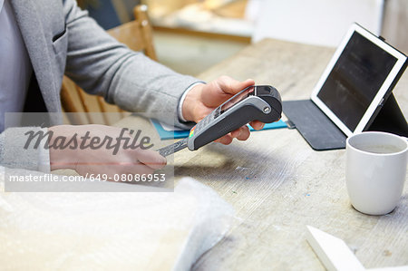 Man buying online with credit card in picture framers workshop Stock Photo - Premium Royalty-Free, Image code: 649-08086953