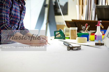 Mid adult man writing measurement on workbench in picture framers workshop Stock Photo - Premium Royalty-Free, Image code: 649-08086958