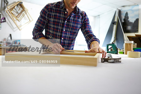 Mid adult man measuring frame on workbench in picture framers workshop Stock Photo - Premium Royalty-Free, Image code: 649-08086959