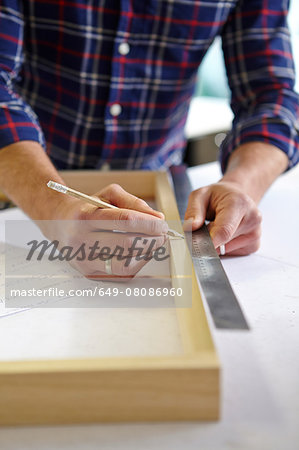 Close up of mid adult man measuring frame on workbench in picture framers workshop Stock Photo - Premium Royalty-Free, Image code: 649-08086960