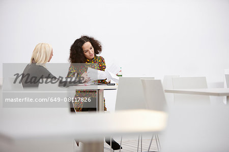 Two businesswomen checking paperwork at office meeting Stock Photo - Premium Royalty-Free, Image code: 649-08117826