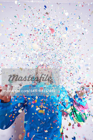 Studio shot of young woman and explosion of confetti Stock Photo - Premium Royalty-Free, Image code: 649-08117841