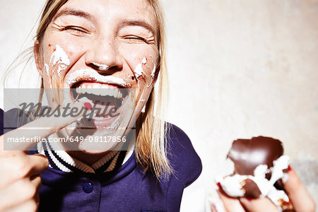 Close up studio shot of young woman with face covered in chocolate marshmallow Stock Photo - Premium Royalty-Free, Image code: 649-08117856