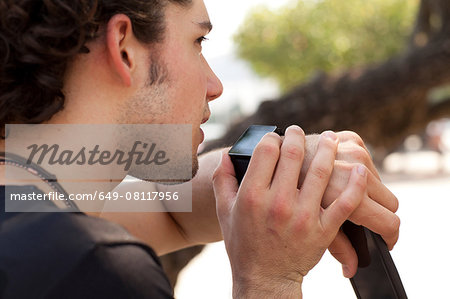Over the shoulder view of young man using smartwatch, Copacabana, Rio De Janeiro, Brazil Stock Photo - Premium Royalty-Free, Image code: 649-08117956