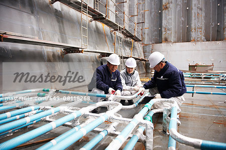 Workers checking pipework on container ship at shipyard, GoSeong-gun, South Korea Stock Photo - Premium Royalty-Free, Image code: 649-08118268