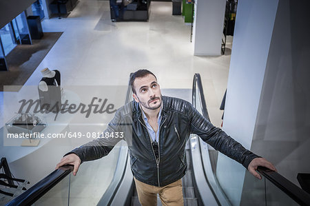 Man moving up escalator in shopping mall Stock Photo - Premium Royalty-Free, Image code: 649-08118433