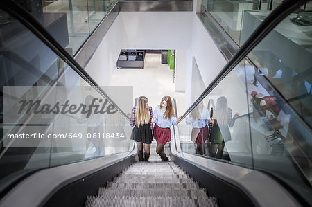 Two female friends moving up escalator in shopping mall Stock Photo - Premium Royalty-Free, Image code: 649-08118434