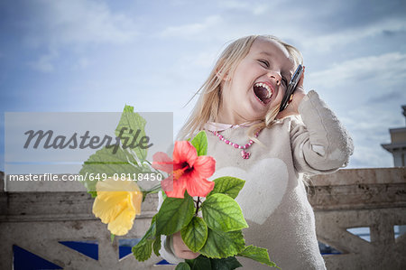 Young girl with flowers laughing and chatting on smartphone, Cagliari, Sardinia, Italy Stock Photo - Premium Royalty-Free, Image code: 649-08118450