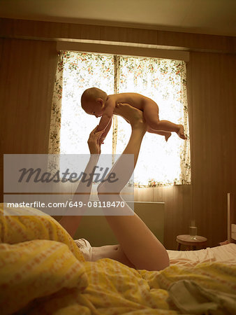 Mother lying on bed balancing baby son on feet Stock Photo - Premium Royalty-Free, Image code: 649-08118470