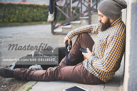 Mid adult man sitting outdoors with dog, using smartphone