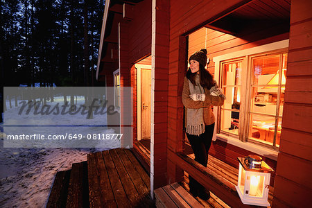 Portrait of young woman looking out from cabin porch at night, Posio, Lapland, Finland Stock Photo - Premium Royalty-Free, Image code: 649-08118777