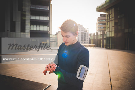Young male runner checking wrist watch in city square Stock Photo - Premium Royalty-Free, Image code: 649-08118831