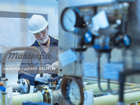 Senior engineer working on pipework in power station Stock Photo - Premium Royalty-Free, Image code: 649-08119194