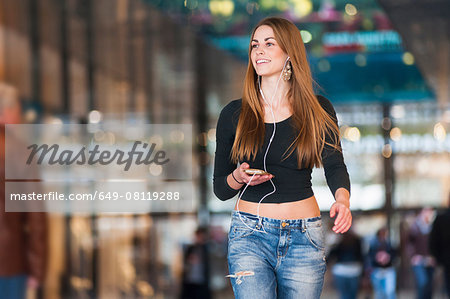 Young woman listening to smartphone music whilst strolling in shopping mall Stock Photo - Premium Royalty-Free, Image code: 649-08119288