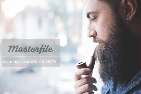 Young bearded man smoking pipe by window Stock Photo - Premium Royalty-Free, Image code: 649-08125276