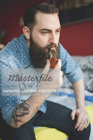 Young bearded man smoking pipe on bed Stock Photo - Premium Royalty-Free, Image code: 649-08125278