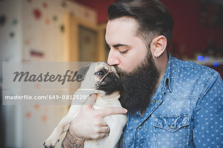 Young bearded man kissing dog in arms Stock Photo - Premium Royalty-Free, Image code: 649-08125280