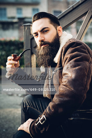 Young bearded man smoking pipe on steps Stock Photo - Premium Royalty-Free, Image code: 649-08125310