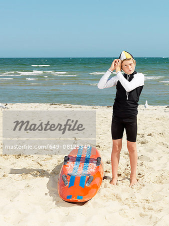 Portrait of boy nipper (child surf life savers) putting on cap, Altona, Melbourne, Australia