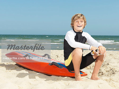 Portrait of confident boy nipper (child surf life savers) sitting on surfboard, Altona, Melbourne, Australia Stock Photo - Premium Royalty-Free, Image code: 649-08125350